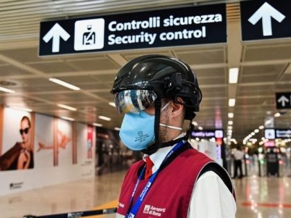 """A Fiumicino airport employee wearing a """"Smart-Helmet"""" portable thermoscanner to screen passengers and staff for COVID-19, stands prepared at boarding gates on May 5, 2020 at Rome's Fiumicino airport during the country's lockdown aimed at curbing the spread of the COVID-19 infection, caused by the novel coronavirus. (Photo by ANDREAS …"""