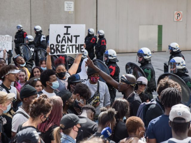 """A woman holds a """"I Can't Breathe"""" sign as Montreal Police and protesters face off during a march against police brutality and racism in Montreal, Canada, on June 7 2020. - On May 25, 2020, Floyd, a 46-year-old black man suspected of passing a counterfeit $20 bill, died in Minneapolis …"""