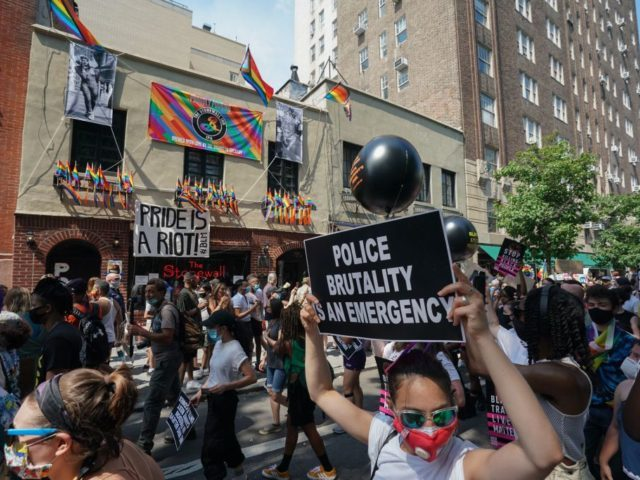 Protesters carrying signs walk past the Stonewall Inn during the Queer Liberation March hosted by The Reclaim Pride Coalition for Trans and Queer black lives and against police brutality in lower Manhattan on June 28, 2020 in New York. (Photo by Bryan R. Smith / AFP) (Photo by BRYAN R. …