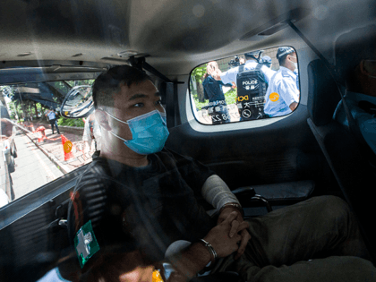 A 23-year-old man, Tong Ying-kit, arrives at a court in a police van in Hong Kong Monday, July 6, 2020. Tong has become the first person in Hong Kong to be charged under the new national security law, for allegedly driving a motorcycle into a group of policemen while bearing …