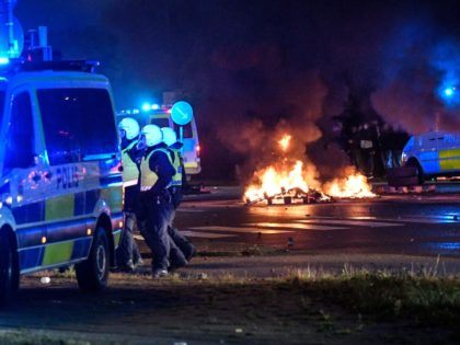 Riot police officers secure the area as smoke billows from burning tyres, pallets and fireworks as a few hundred protesters riot in the Rosengard neighbourhood of Malmo, Sweden, on August 28, 2020. - The protest was sparked by the burning of a coran by members of Danish far-right party Stram …