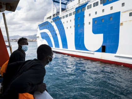 Two migrants ob board the Sea-Watch 4 civil sea rescue ship look on as they approach a ferry at sea off the coast of Palermo, Sicily, Italy, on September 02, 2020, in order to disembark some 350 migrants who will be under quarantine. - More than 350 migrants including those …