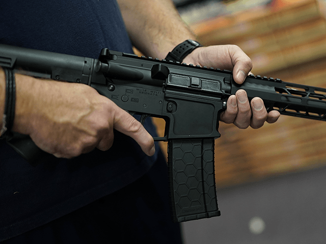 A customer handles an AR-15 at Jimmy's Sport Shop in Mineola, New York on September 25, 2020. - Gun store owners on Long Island have been selling out of firearms as scores of customers fear a rise in violence as the pandemic escalates in the area. (Photo by TIMOTHY A. …