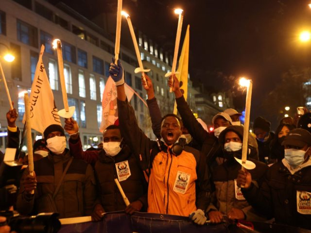 Protesters hold candles during a demonstration for the regularisation of migrants at the occasion of the International Migrants Day, on December 18, in Paris. (Photo by THOMAS COEX / AFP) (Photo by THOMAS COEX/AFP via Getty Images)