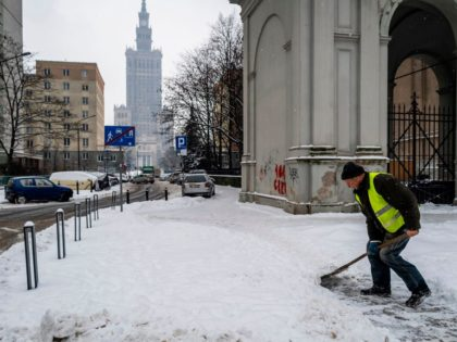 A municipal worker clears the sidewalk from snow in the center of Warsaw, February 10, 2021, after a few days of snowfall, Warsaw wasplunged into a winter that has not been seen here in several years. (Photo by Wojtek RADWANSKI / AFP) (Photo by WOJTEK RADWANSKI/AFP via Getty Images)