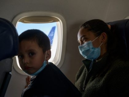 "TOPSHOT - Central American migrants Lidia and Isaac sit aboard their flight on March 30, 2021 from McAllen to Houston after being released from a US government holding facility for illegal migrants seeking asylum in McAllen, Texas. - ""Please help me, I don't speak English, ""a manila envelope reads in …"