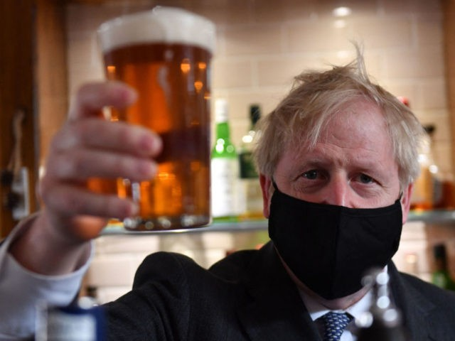 Britain's Prime Minister and leader of the Conservative Party, Boris Johnson, wearing a face covering due to Covid-19, poses after he poured a pint of beer at during a visit to The Mount Tavern pub and restaurant in Wolverhampton, central England, on April 19, 2021, while campaigning for the upcoming …
