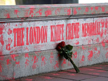 A bouquest is left at a mural to highlight knife crime in London on April 30, 2021. (Photo by Tolga Akmen / AFP) (Photo by TOLGA AKMEN/AFP via Getty Images)