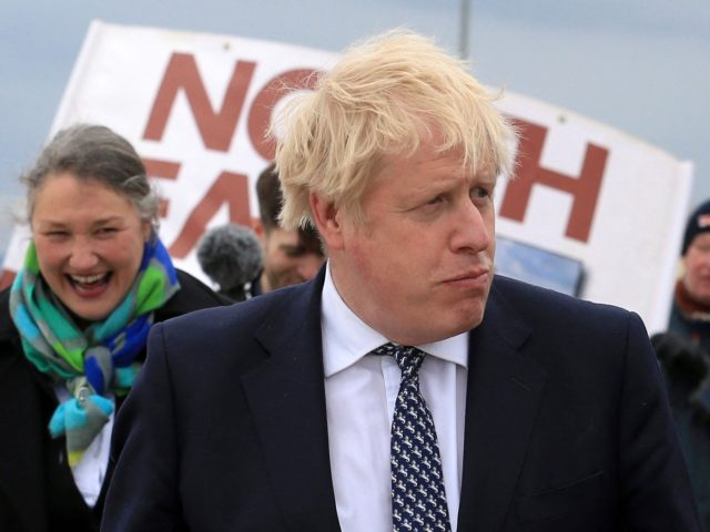 Britain's Prime Minister Boris Johnson (R) reacts as he campaigns on behalf of Conservative Party candidate Jill Mortimer (L) in Hartlepool, north-east England on May 3, 2021, ahead of the 2021 Hartlepool by-election to be held on May 6. (Photo by Lindsey Parnaby / POOL / AFP) (Photo by LINDSEY …