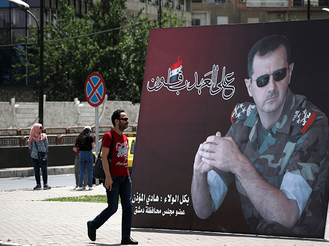 A Syrian man walks past a giant portrait of President Bashar al-Assad at the Umawiyin square in Syria's capital Damascus on May 3, 2021, ahead of this month's presidential elections. - A Syrian former minister and a member of the Damascus-tolerated opposition will face Bashar al-Assad in this month's presidential …