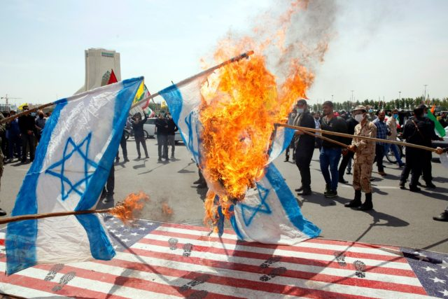 Iranians set Israeli flags on fire as they step on a US flag during a rally marking al-Quds Day (Jerusalem) day, at the capital Tehran's Azadi (Freedom) square, on May 7, 2021. - An initiative started by the late Iranian revolutionary leader Ayatollah Ruhollah Khomeini, Quds Day is held annually …