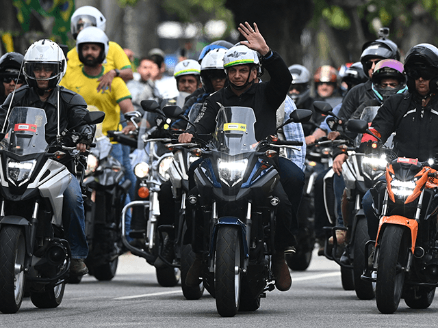 Brazilian President Jair Bolsonaro (C) gestures as he heads a motorcade rally with his supporters in Rio de Janeiro, Brazil, on May 23, 2021. - Bolsonaro led a procession of several thousand motorcycles that marched through the streets of Rio de Janeiro for a demonstration in his support, sparking numerous …