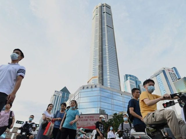 People walk past the temporarily closed of 300-meter (1,000-ft.) SEG Plaza (C) in the southern Chinese city of Shenzhen, in Guangdong province on May 24, 2021, nearly a week after it began to shake unexpectedly, triggering widespread panic, with people fleeing the streets below. (Photo by Noel Celis / AFP) …