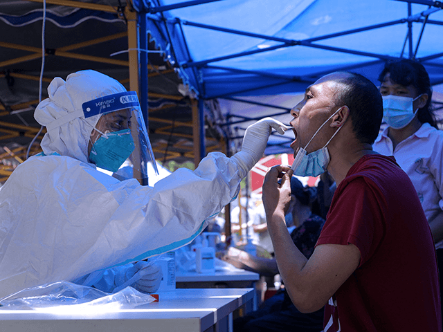 This photo taken on May 30, 2021 shows a man receiving a nucleic acid test for the Covid-19 coronavirus in Guangzhou in China's southern Guangdong province. - China OUT (Photo by STR / AFP) / China OUT (Photo by STR/AFP via Getty Images)
