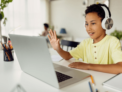 boy using laptop and waving during video call while homeschooling