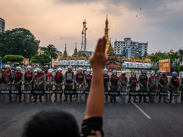 A protester makes a three-finger salute in front of a row of riot police, who are holding roses given to them by protesters, on February 06, 2021 in Yangon, Myanmar. Myanmar's military junta on Saturday placed heavy restrictions on internet connections and suspended more social media services, almost a week …
