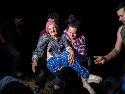 ROMA, TEXAS - APRIL 29: Honduran immigrant Trinidad Tabora, 93, is carried onto the U.S. bank of the Rio Grande on April 29, 2021 in Roma, Texas. She and her granddaughter (C) were smuggled across the border with other Central American asylum seekers during the early hours of the morning. …