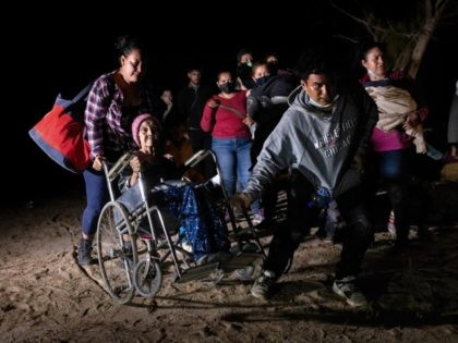 ROMA, TEXAS - APRIL 29: Honduran immigrant Trinidad Tabora, 93, is wheeled from the bank of the Rio Grande after crossing the border from Mexico on April 29, 2021 in Roma, Texas. She and her granddaughter (L) were smuggled across the border with other Central American asylum seekers during the …