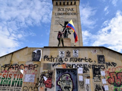 BOGOTA, COLOMBIA - MAY 04: A demonstrator waves a Colombian flag next to the monument of Simon Bolivar during a protest against the government of President Ivan Duque on May 04, 2021 in Bogota, Colombia. Violent clashes between protestors and riot police continue after President Duque ordered Congress the withdrawal …