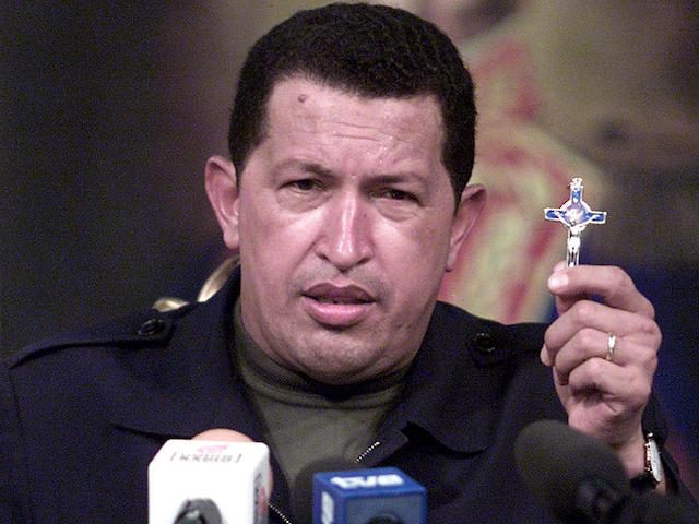 Venezuelan President Hugo Chavez holds a crucifix as he addresses the nation from the Miraflores presidential palace 14 April 2002 in Caracas. An emotional Chavez returned to the presidency of Venezuela 14 April 2002 after a two-day sojourn as a leader ousted in a coup d'etat. (Photo credit should read …