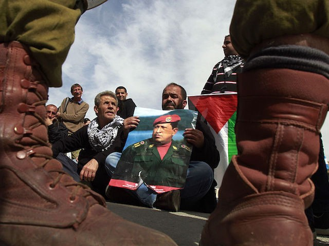 A Palestinian protestor holds a picture of late Venezuelan President Hugo Chavez during a weekly demonstration against Israeli occupation in the West Bank village of Maasarah near Bethlehem on March 8, 2013. Palestinians in Gaza and the West Bank were united in grief over the death of Venezuela's Hugo Chavez, …