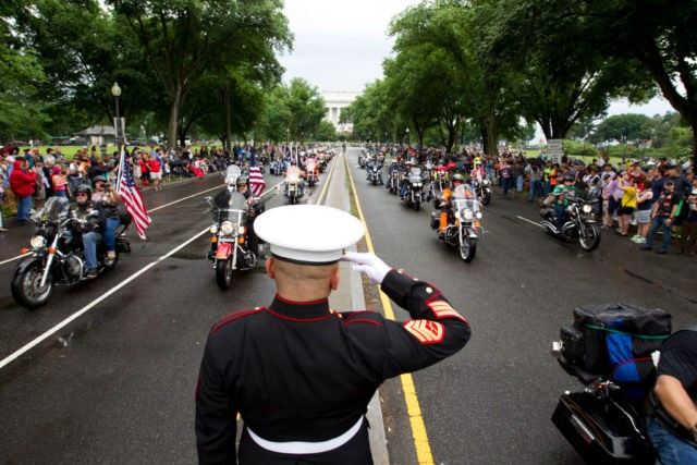 TOPSHOT - US Marine Tim Chambers salutes as participants in the Rolling Thunder annual motorcycle rally ride in Washington DC, on May 28, 2017. Motorcyclists are in Washington for the traditional annual Rolling Thunder ahead of Memorial Day, May 29. / AFP PHOTO / Jose Luis Magana (Photo credit should …