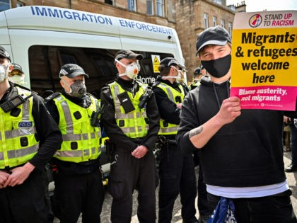 GLASGOW, SCOTLAND - MAY 13: Protestors block an immigration enforcement van, stopping it from leaving Kenmure Street in First Minister, Nicola Sturgeon's constituency on May 13, 2021 in Glsgow, Scotland. Police officers were called to Kenmure Street in Pollokshields, on the south side of the city, to support the UK …