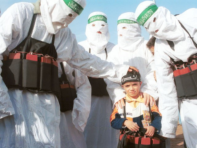 Palestinians dressed as suicide bombers, put fake explosives on a small child December 9, 2001 after marching in commemoration of the 14th anniversary of the Palestinian militant group, Hamas, in Ain El Helweh, the largest Palestinian refugee camp in Lebanon. The camp is home to more than 40,000 Palestinian refugees …