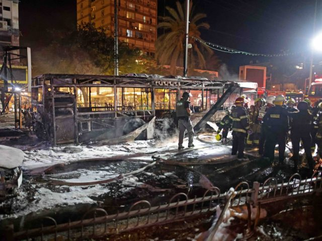 Israeli firefighters check out a burnt bus in the Israeli town of Holon near Tel Aviv, on May 11, 2021, after rockets are launched towards Israel from the Gaza Strip controlled by the Palestinian Hamas movement. (Photo by ahmad gharabli / AFP) (Photo by AHMAD GHARABLI/AFP via Getty Images)