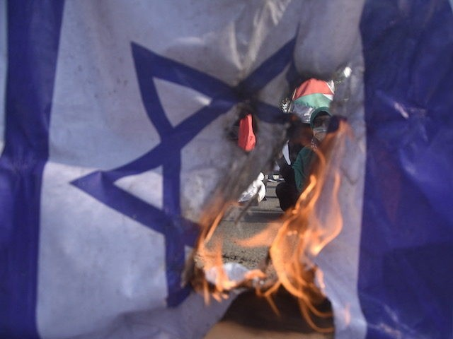 Demonstrators burn an Israeli flag during a protest against Israel's attacks on the Palestinian Gaza Strip, in Bekasi on May 25, 2021. (Photo by Rezas / AFP) (Photo by REZAS/AFP via Getty Images)