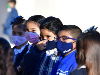 A students adjusts her facemask at St. Joseph Catholic School in La Puente, California on November 16, 2020, where pre-kindergarten to Second Grade students in need of special services returned to the classroom today for in-person instruction. - The campus is the second Catholic school in Los Angeles County to …