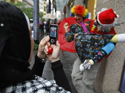 A Muslim woman takes a picture with her mobile of clowns and street performers in Beirut's Hamra shopping district on December 9, 2008. Thirty performers from Germany, Italy, Morocco and Lebanon donned rainbow-coloured wigs and round red plastic noses put on a show in the streets as frustrated drivers blasted …
