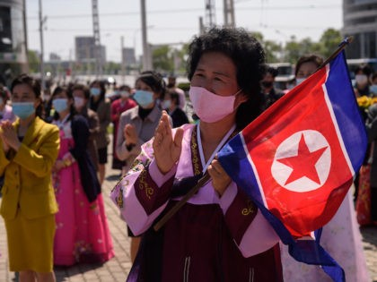 A woman wearing traditional dress and holding a North Korean flag watches a performance celebrating the 89th anniversary of the founding of the Korean People's Revolutionary Army, a precursor to the Korean People's Army (KPA), in Changjon Street in Pyongyang on April 25, 2021. (Photo by KIM Won Jin / …