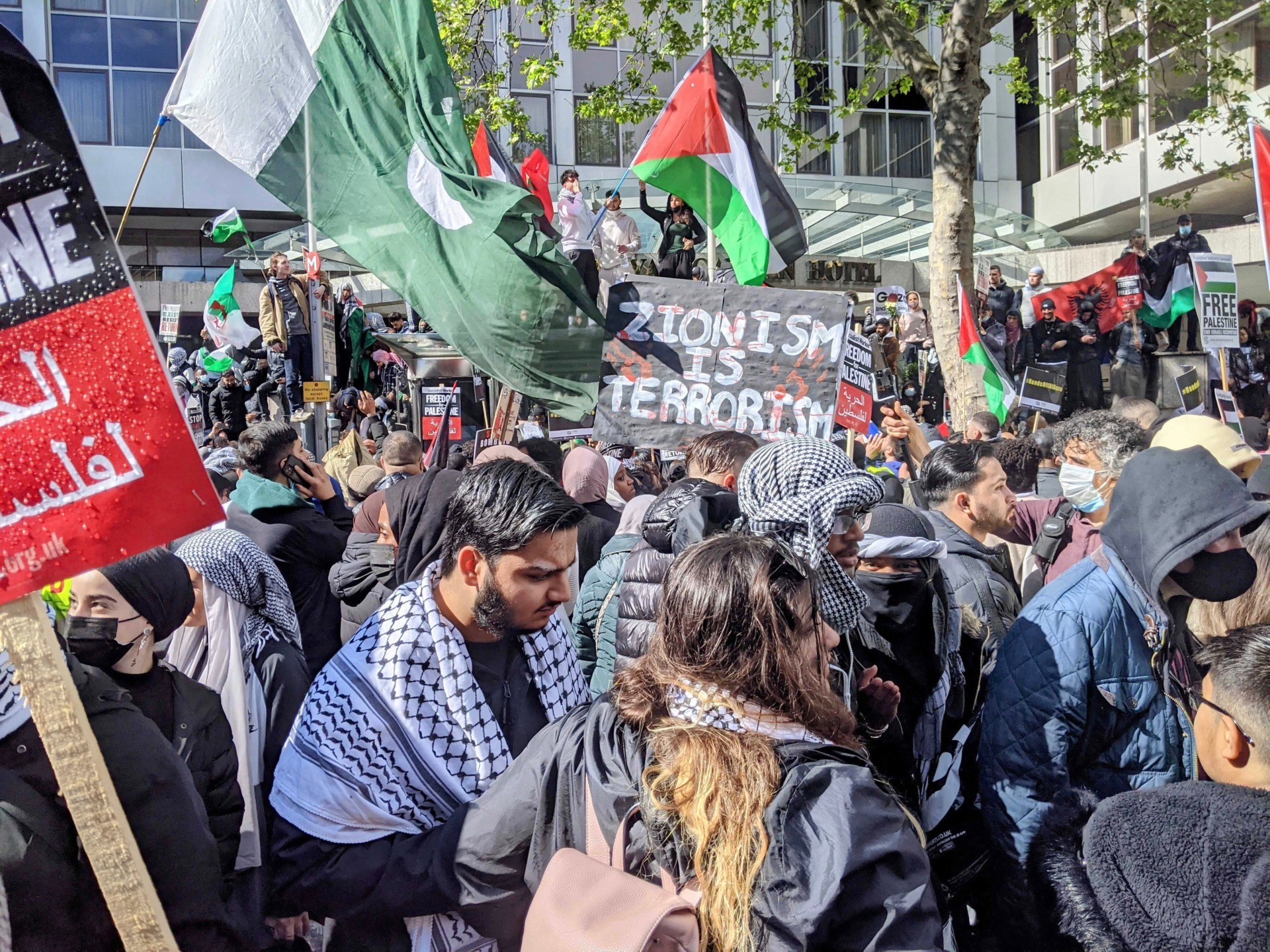 """A protester is seen carrying a placard reading """"Zionism is Terrorism"""", at an anti-Israel protest in London. May 15th, 2021. Kurt Zindulka, Breitbart News"""