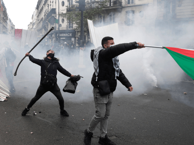 A protester throws a metal bar during a demonstration in solidarity with the Palestinians called over the ongoing conflict with Israel in Paris on May 15, 2021. - Police officers used tear gas and water cannon in Paris to try and disperse a pro-Palestinian rally held despite a ban by …
