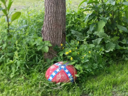 A New York mother has been ordered to dispose of a rock near her driveway bearing a small Confederate flag or risk losing custody of her mixed race child.Provided by lawyer
