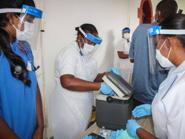 A medical personel unpacks the Chinese Covid-19 vaccine produced by Sinopharm at the Seychelles Hospital in Victoria, on January 10, 2021. - More than 1.9 million people worldwide have now died from the virus, with new variants adding to soaring cases and prompting the re-introduction of restrictions on movement across …