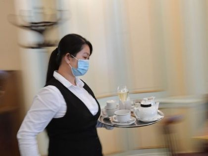 A waitress carries a tray at cafe Einstein in Berlin on May 15, 2020, as lockdown measures were eased and cafes and restaurants were allowed to reopen amid the novel coronavirus / COVID-19 pandemic. (Photo by Tobias SCHWARZ / AFP) (Photo by TOBIAS SCHWARZ/AFP via Getty Images)