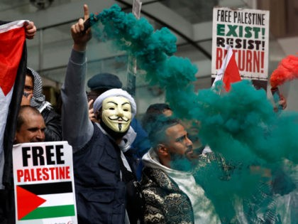 TOPSHOT - Pro-Palestinian activists and supporters let off smoke flares, wave flags and carry placards during a demonstration in support of the Palestinian cause as violence escalates in the ongoing conflict with Israel, outside the Israeli embassy in central London on May 15, 2021. (Photo by Tolga Akmen / AFP) …