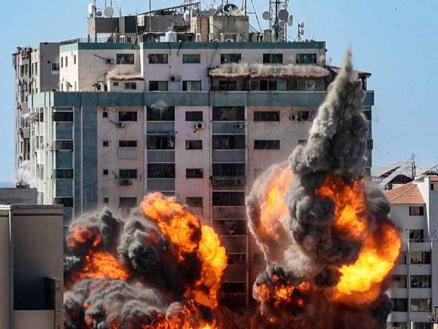 TOPSHOT - A ball of fire erupts from the Jala Tower as it is destroyed in an Israeli airstrike in Gaza City, controlled by the Palestinian Hamas movement, on May 15, 2021. - Israeli air strikes pounded the Gaza Strip, killing 10 members of an extended family and demolishing a …