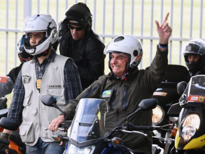 Brazil's President Jair Bolsonaro waves to supporters as he rides a motorcycle leading a caravan of more than 1000 bikers to celebrate Mother's Day in Brasilia on May 9, 2021. (Photo by EVARISTO SA / AFP) (Photo by EVARISTO SA/AFP via Getty Images)