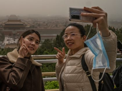 BEIJING, CHINA - MARCH 28: Chinese tourists take their photo with the Forbidden City in the background from Jingshan Park during a sandstorm on March 28, 2021 in Beijing, China. China's capital and the northern part of the country was hit with a sandstorm Sunday, sending air quality indexes of …