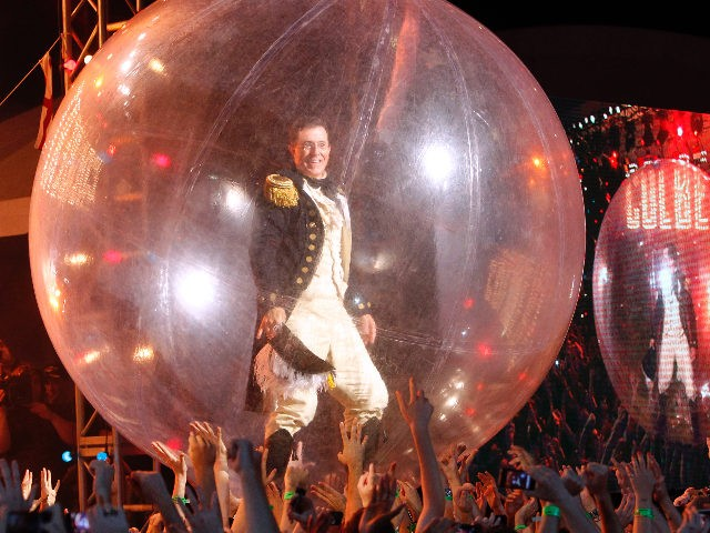 Stephen Colbert is supported by audience members while standing inside a large inflatable bubble during the finale of StePhest Colbchella '012 Rocktaugustfest at the Intrepid Sea, Air & Space Museum, Friday, Aug. 10, 2012, in New York. (Photo by Jason DeCrow/Invision/AP)