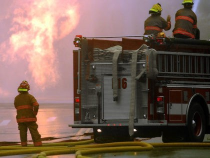 A Little Rock, Ark., firefighter watches as colleagues spray water onto a gas line fire Monday, Nov. 1, 2004, in Little Rock. Flames were leaping from an intersection in the city's west side. (AP Photo/Danny Johnston)