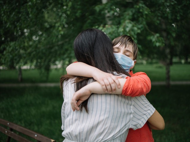Portrait of mother and daughter cuddling in park during coronavirus pandemic - stock photo Portrait of mother and daughter cuddling in park during coronavirus pandemic. Young girl with protection mask embracing woman outdoor.
