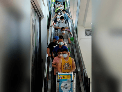 Shoppers, wearing face masks after Taiwan bumped up its alert level in some locations in the wake of a new wave of Covid-19 coronavirus infections, ride down an escalator at a shopping mall in New Taipei City on May 15, 2021. (Photo by Sam Yeh / AFP) (Photo by SAM …