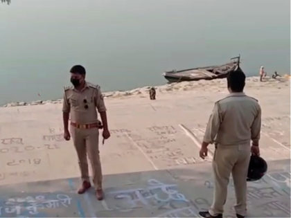 This frame grab from video provided by KK Productions shows police officials stand guard at the banks of the river where several bodies were found lying in Ghazipur district in Uttar Pradesh state India, Tuesday, May 11, 2021. Scores of dead bodies have been found floating down the Ganges River …
