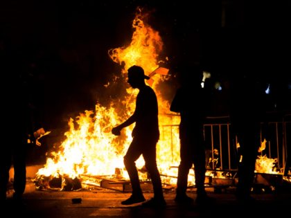 JERUSALEM, ISRAEL - MAY 08: Palestinians stand next to a burning barricade during clashes with Israeli police officers during the holy month of Ramadan on May 8, 2021 in Jerusalem, Israel. Tensions continue in Jerusalem's Old City after clashes in Al-Aqsa Mosque where dozens of Palestinians were seriously injured. (Photo …