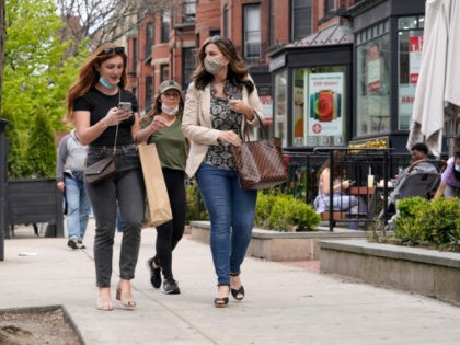 Pedestrians walk along Boston's fashionable Newbury Street, Sunday, May 2, 2021. In Massachusetts as of Friday, April 30, 2021, masks are only required outside in public when it's not possible to maintain a distance of approximately 6 feet from others, or when required for other reasons, including at outdoor events. …