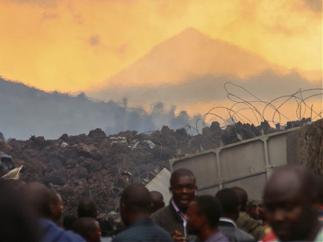 Residents check the damages caused by lava from the overnight eruption of Mount Nyiragongo, seen in background, in Buhene, on the outskirts of Goma, Congo in the early hours of Sunday, May 23, 2021. Congo's Mount Nyiragongo erupted for the first time in nearly two decades Saturday, turning the night …